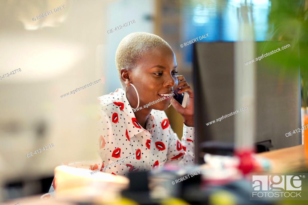 Stock Photo: Businesswoman talking on smart phone, working at computer in office.