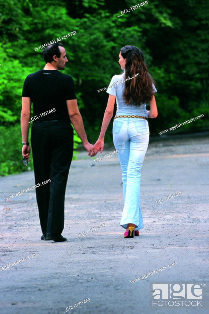 Stock Photo: couple holding hands in a park.