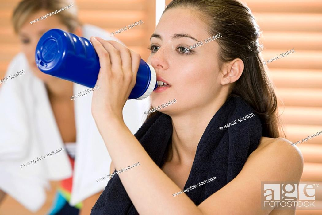 Stock Photo: Woman drinking at gym.