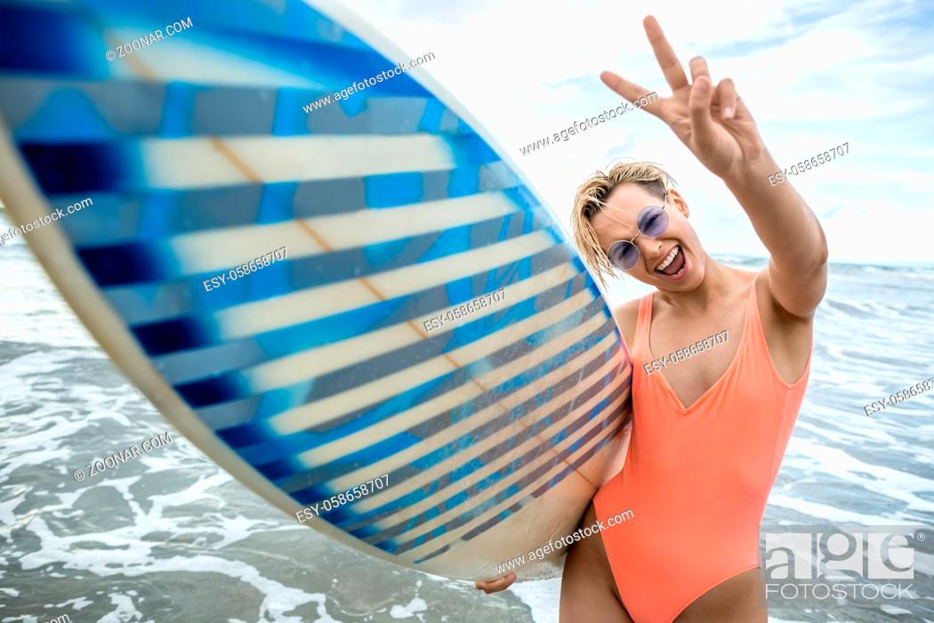 Stock Photo: Joyful blonde girl with short hairstyle stands on the beach on the background of the sea and cloudy sky. She wears orange swimsuit with sunglasses and holds a.