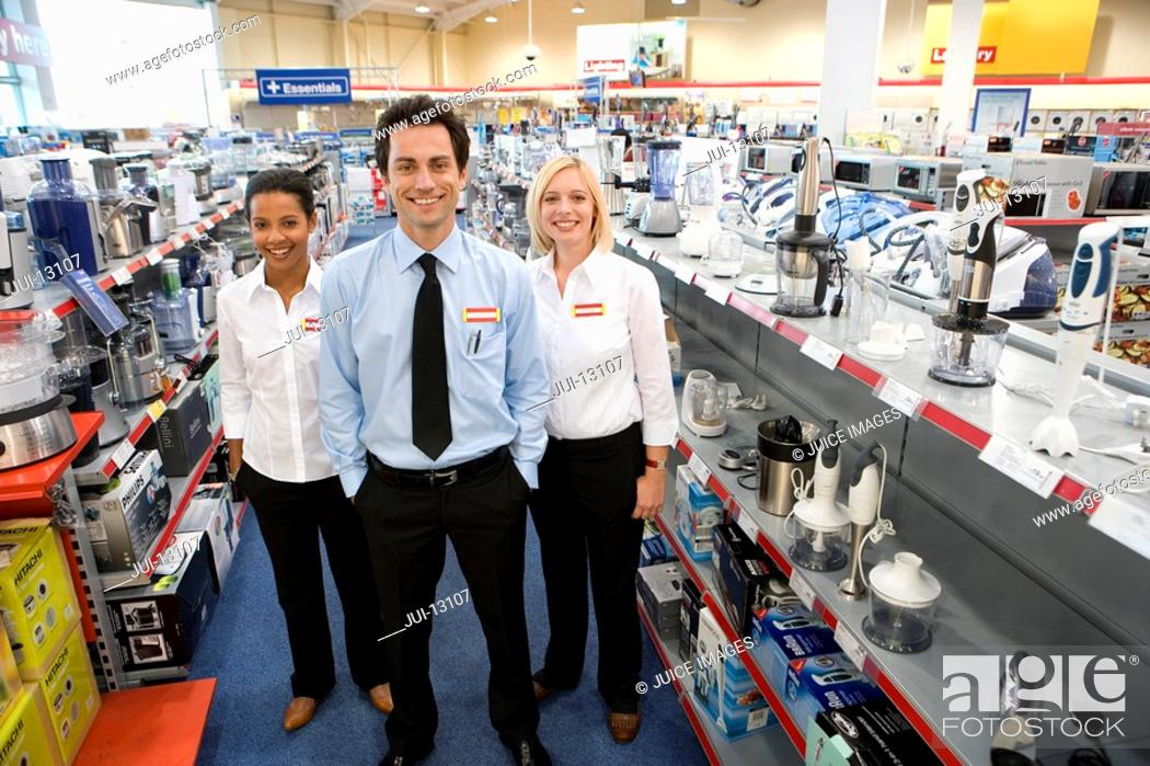Stock Photo: Young salesman flanked by female colleagues in shop, smiling, portrait.