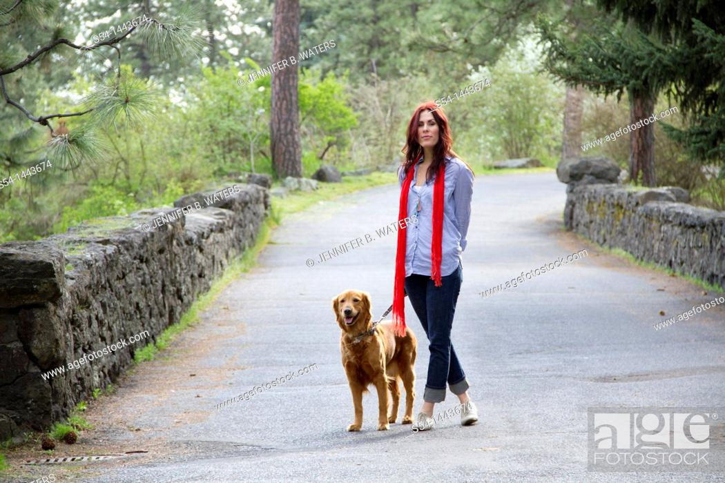 Stock Photo: A woman outdoors with her Golden Retriever.