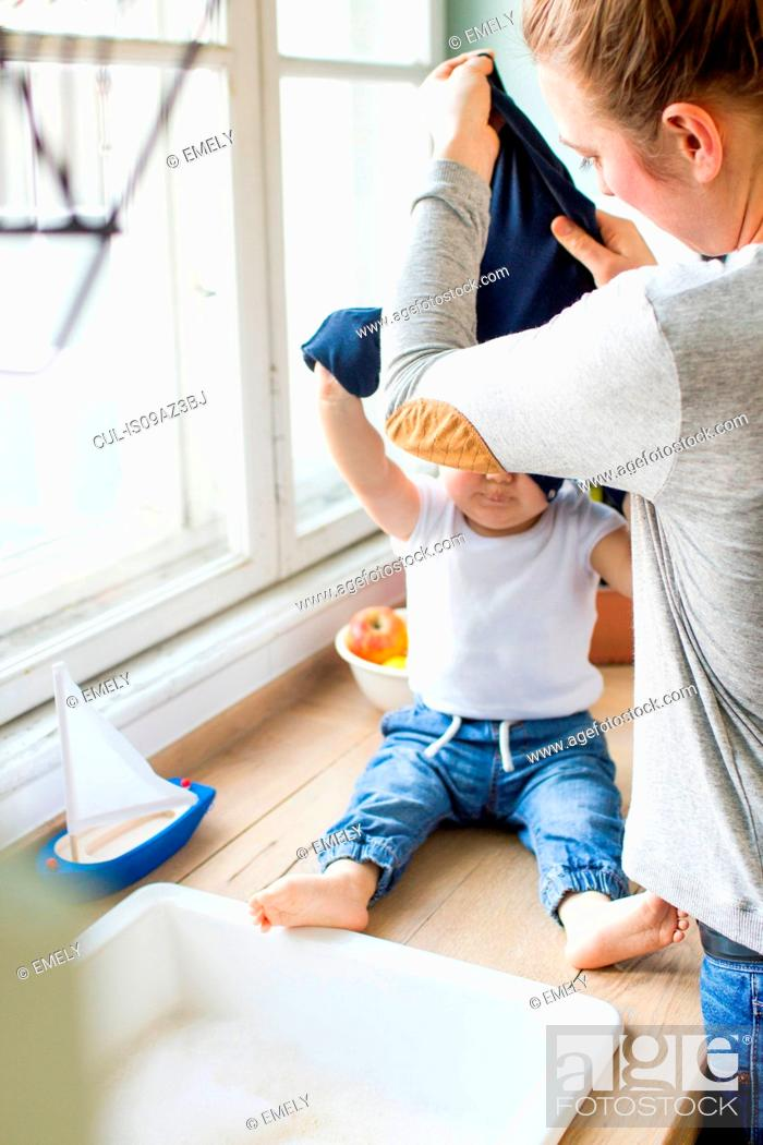 Stock Photo: Woman undressing baby son at kitchen sink.