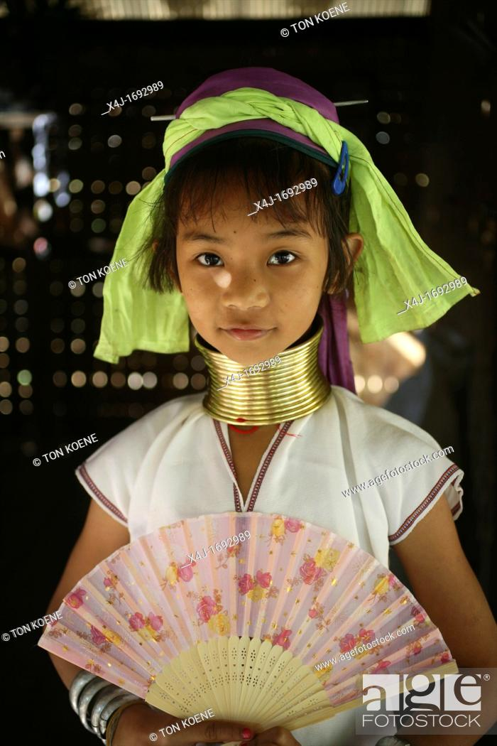 Stock Photo: Portrait of a young Longneck girl with a fan Approximately 300 Burmese refugees in Thailand are members of the indigenous group known as the Longnecks The.