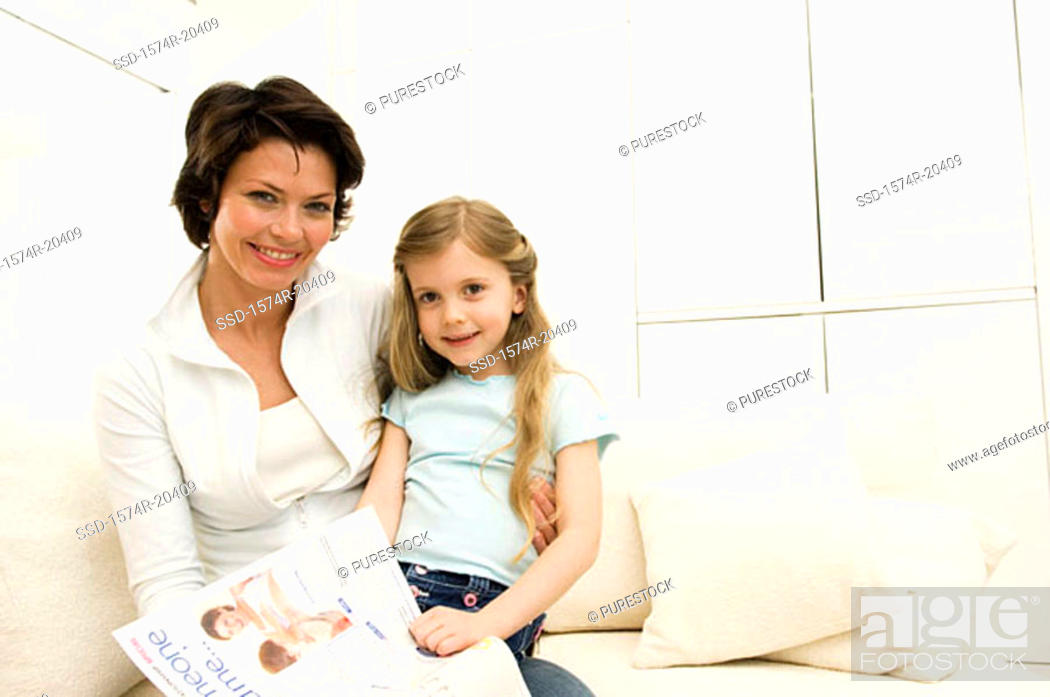 Stock Photo: Portrait of a girl sitting on her mother's lap on a couch.