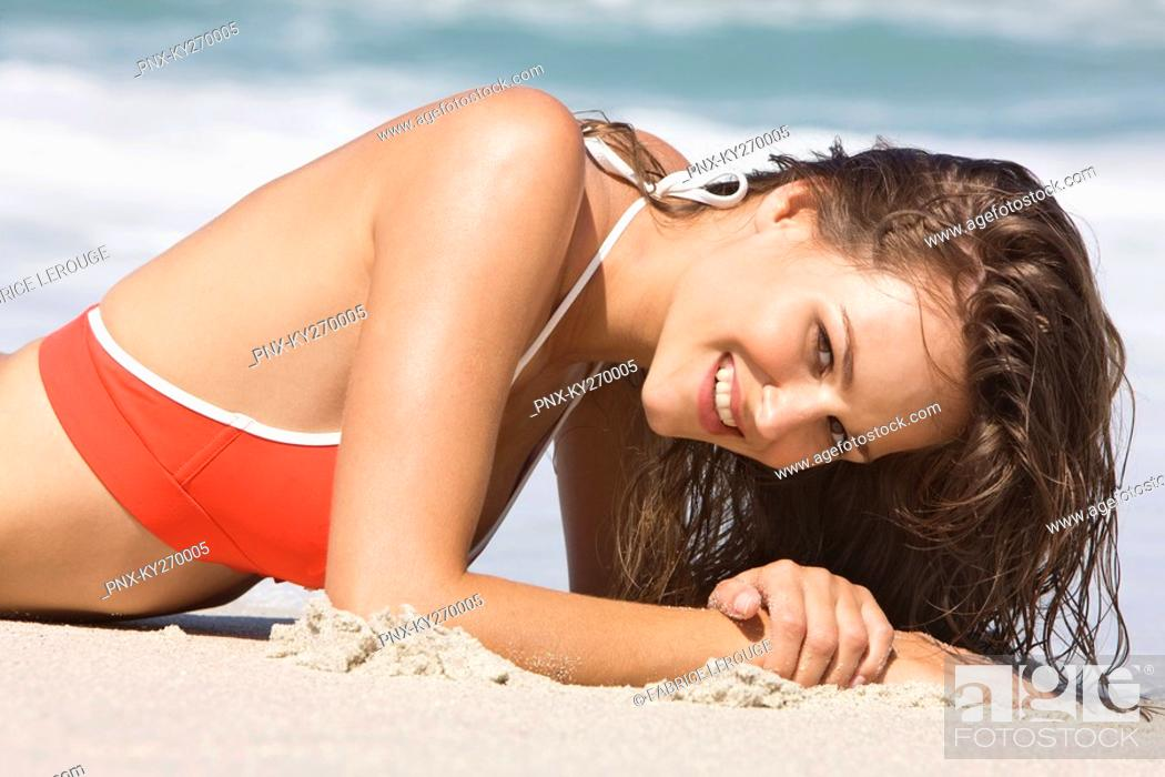 Stock Photo: Portrait of a woman lying on the beach.