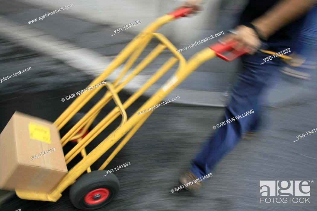 Stock Photo: delivery man walking in street road in city town.