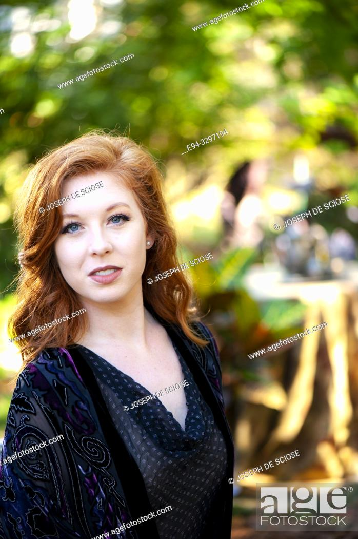 Stock Photo: Portrait of a 25 year old redheaded woman in a garden setting.