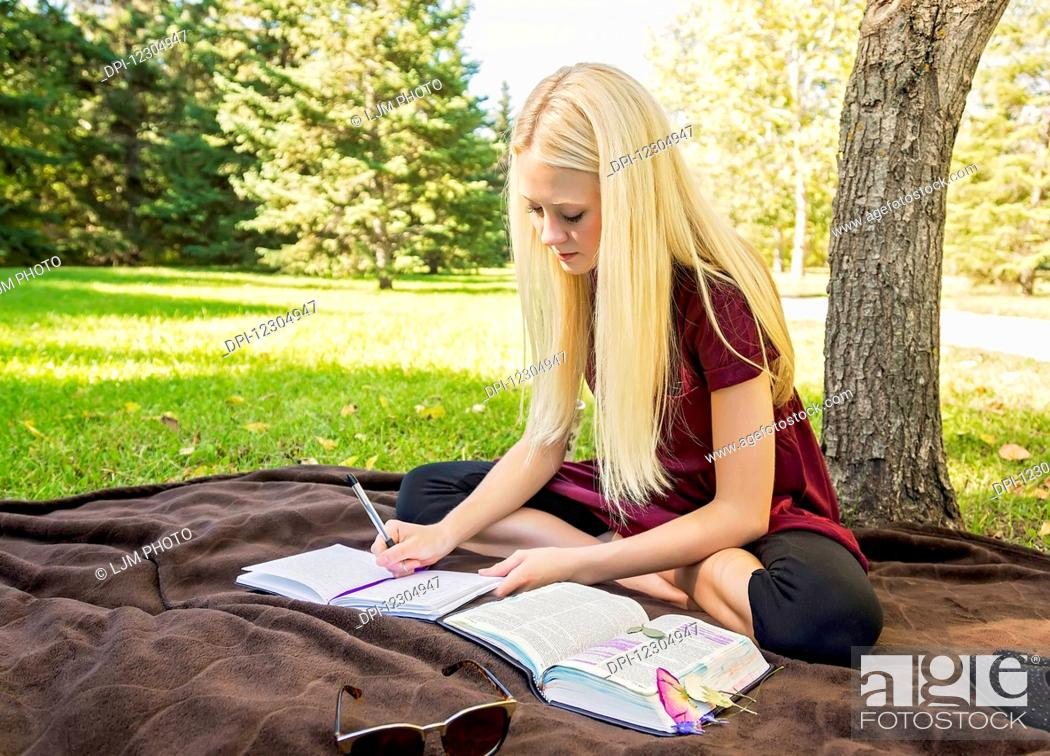Photo de stock: A young woman with long blond hair spending personal time in Bible study outdoors in a park in autumn; Edmonton, Alberta, Canada.