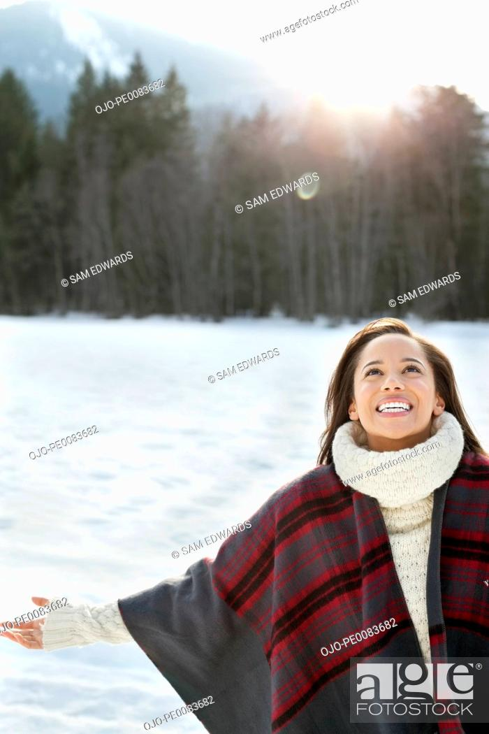 Stock Photo: Smiling woman with head back and arms outstretched in snow.