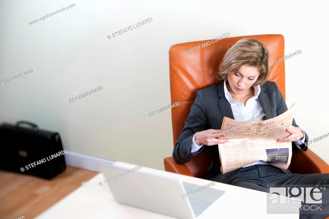 Stock Photo: Business woman reading newspaper in her office, high angle view.
