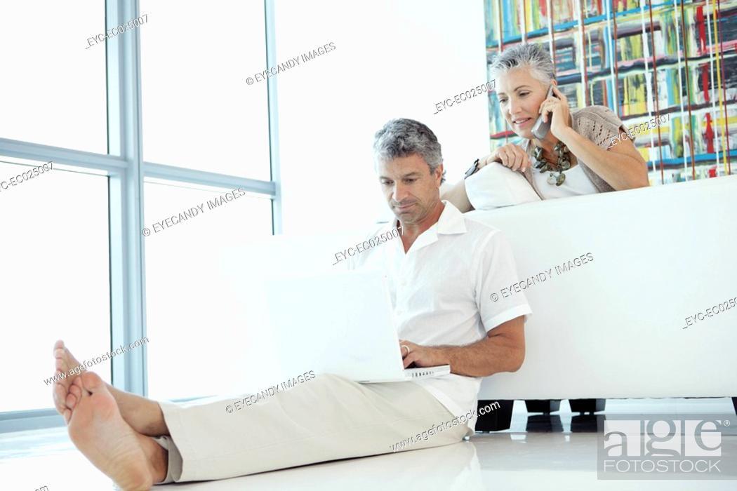 Stock Photo: Mature couple using laptop and telephone.