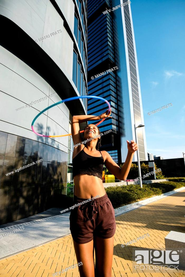 Stock Photo: Sporty woman exercising with plastic hoops on sidewalk outside office buildings.