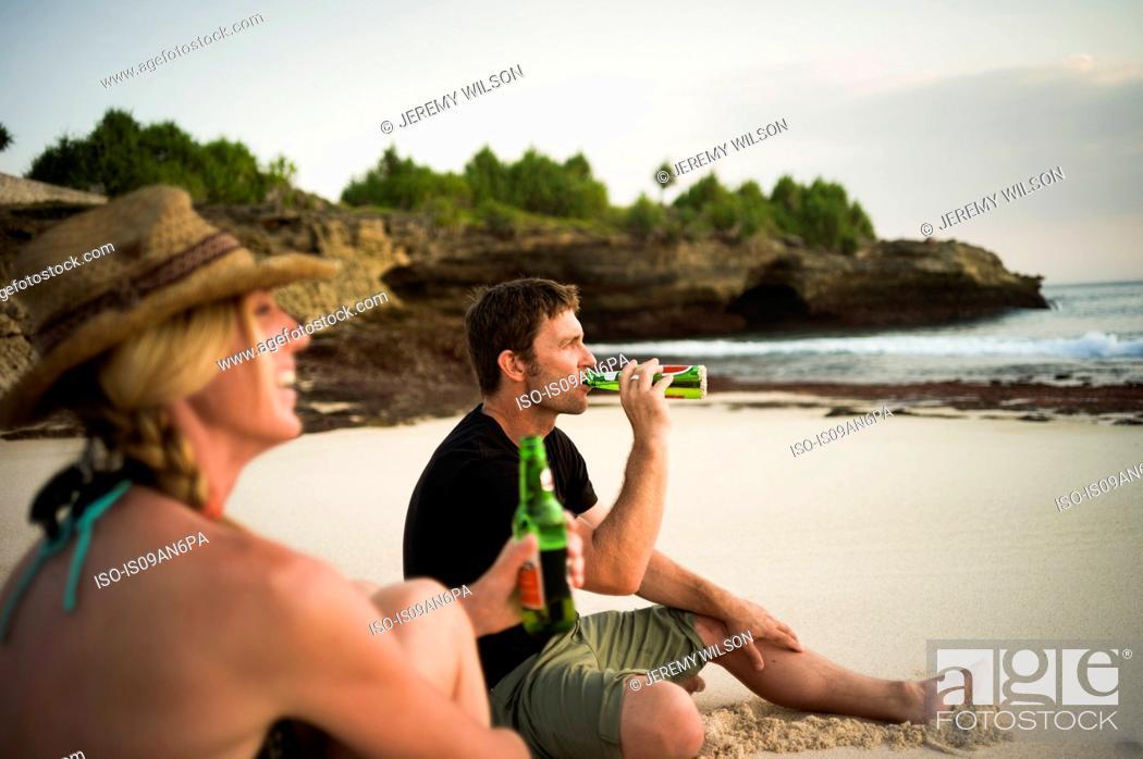 Stock Photo: Couple sitting on beach, drinking beer, Nusa Lembongan, Indonesia.