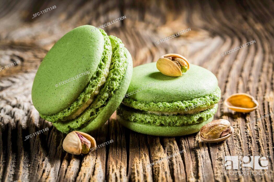 Photo de stock: Green pistachio macaroons on a wooden table.