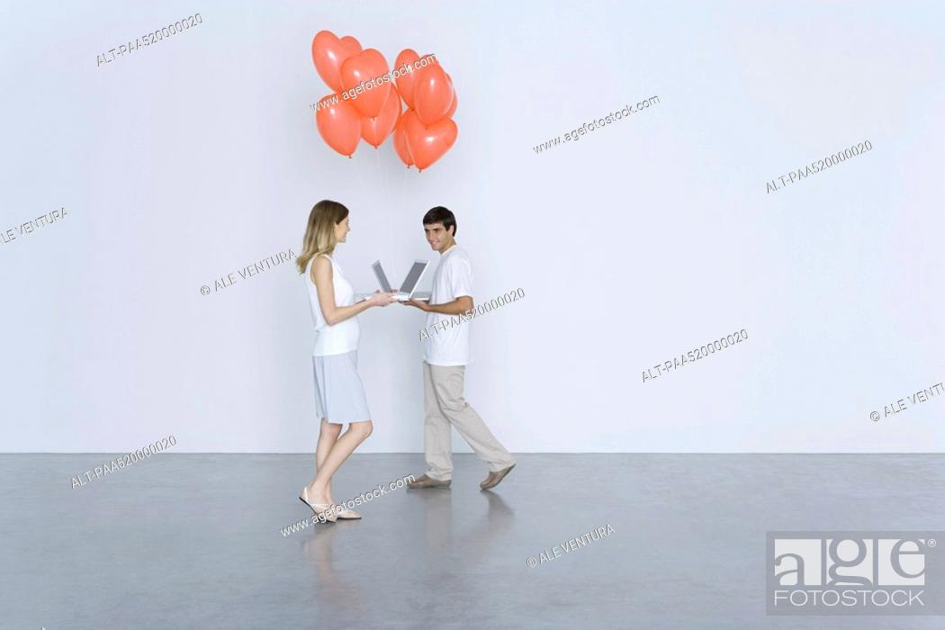 Stock Photo: Man and woman walking toward each other with laptop computers and heart balloons, smiling.