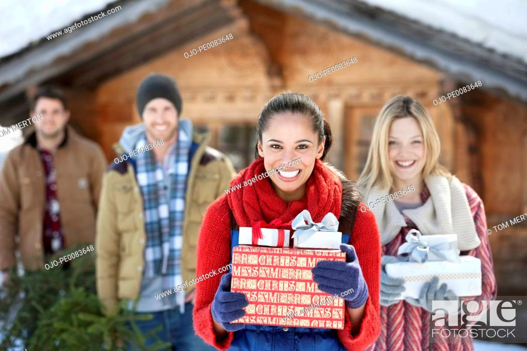 Stock Photo: Portrait of smiling couples holding fresh cut Christmas tree and gifts.