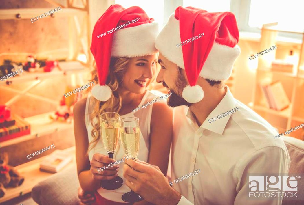 Stock Photo: Beautiful young couple in Santa hats is holding glasses of champagne and smiling while celebrating New Year at home.