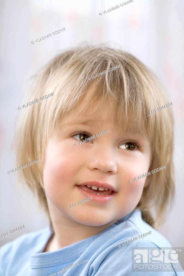 Stock Photo: A young boy smiling and looking away.