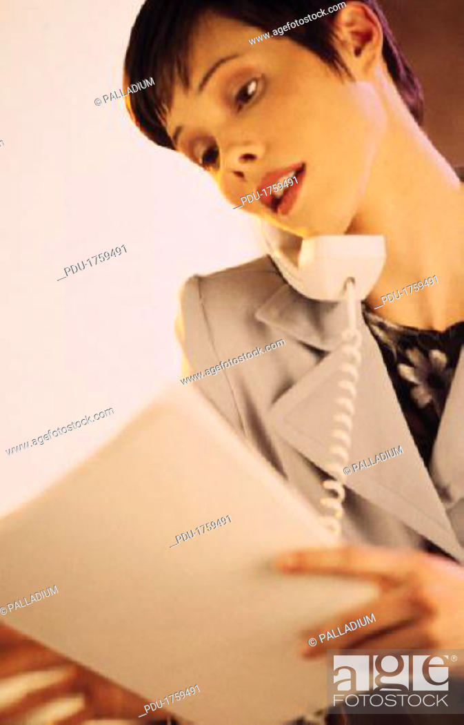 Stock Photo: Business woman talking on telephone, reviewing paperwork.