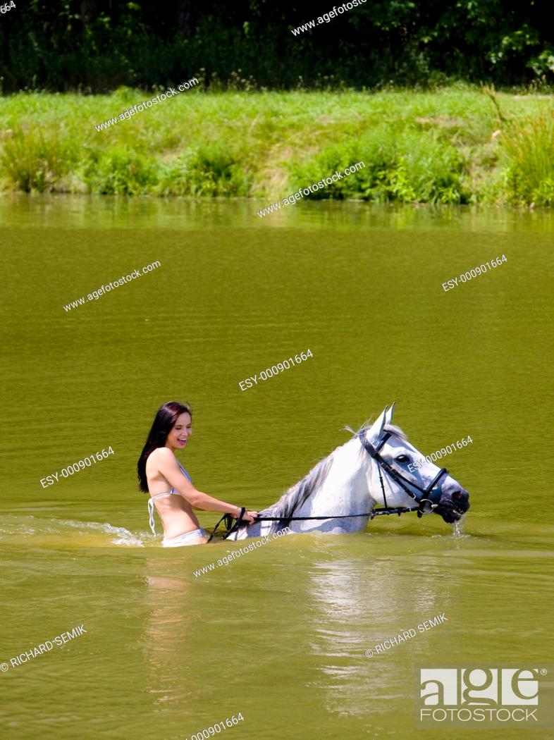 Stock Photo: equestrian on horseback riding through water.