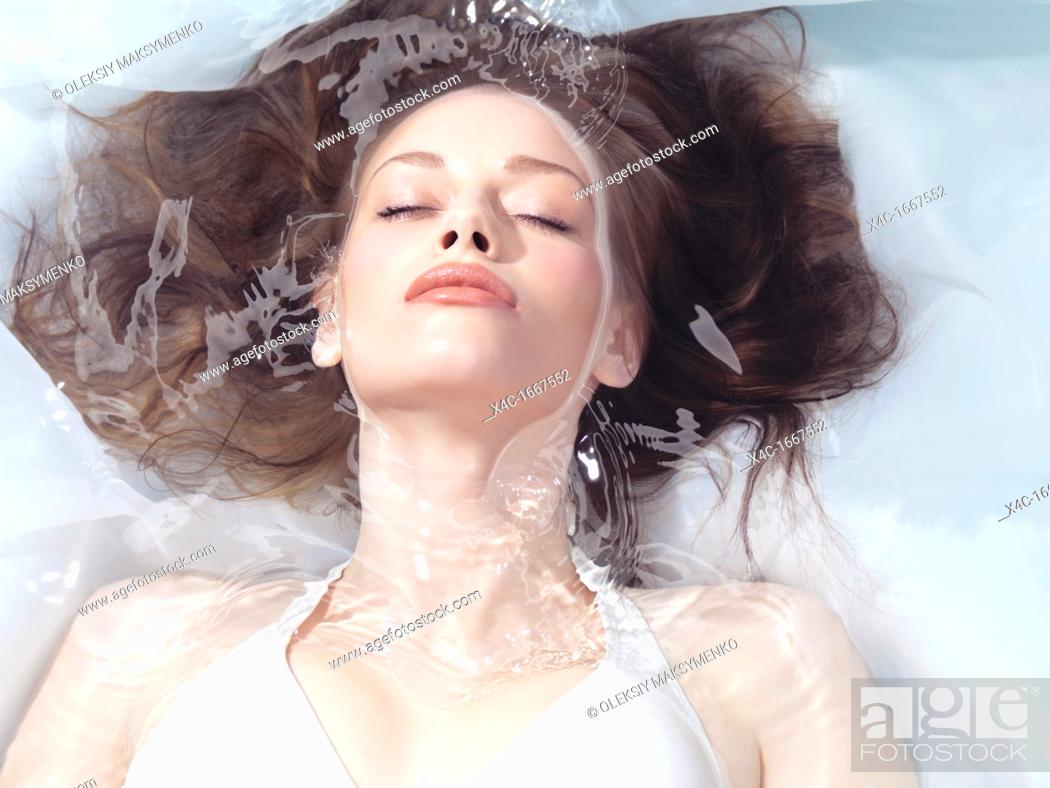 Stock Photo: Natural look beauty portrait of a young woman lying relaxed in water with closed eyes  Beauty treatment concept.