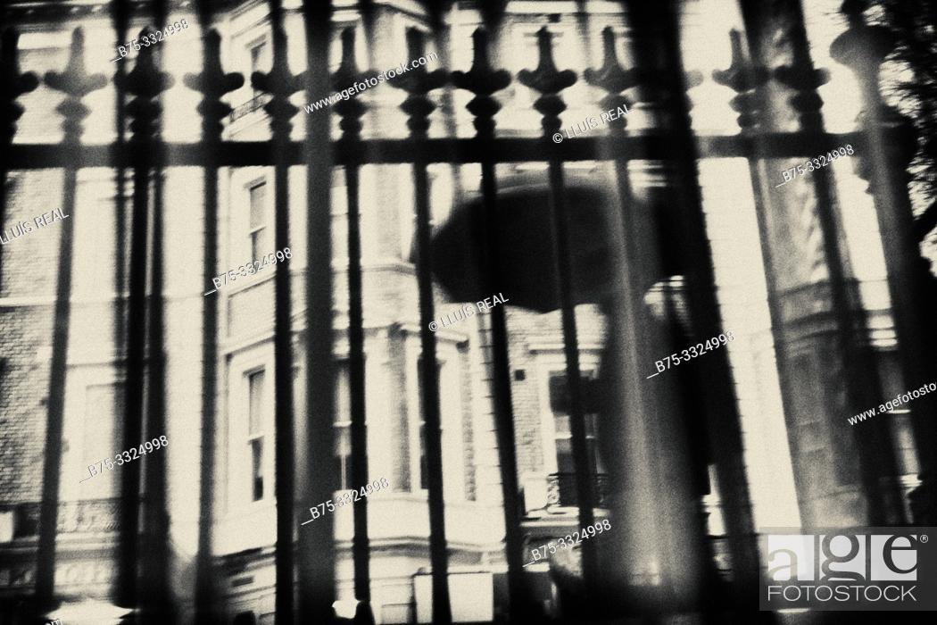 Stock Photo: Silhouette of an unrecognizable man with an umbrella walking on a rainy day in the City seen through a fence. London, UK, Europe.