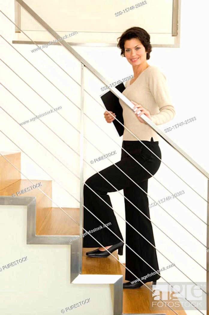 Stock Photo: Portrait of a businesswoman climbing up stairs.