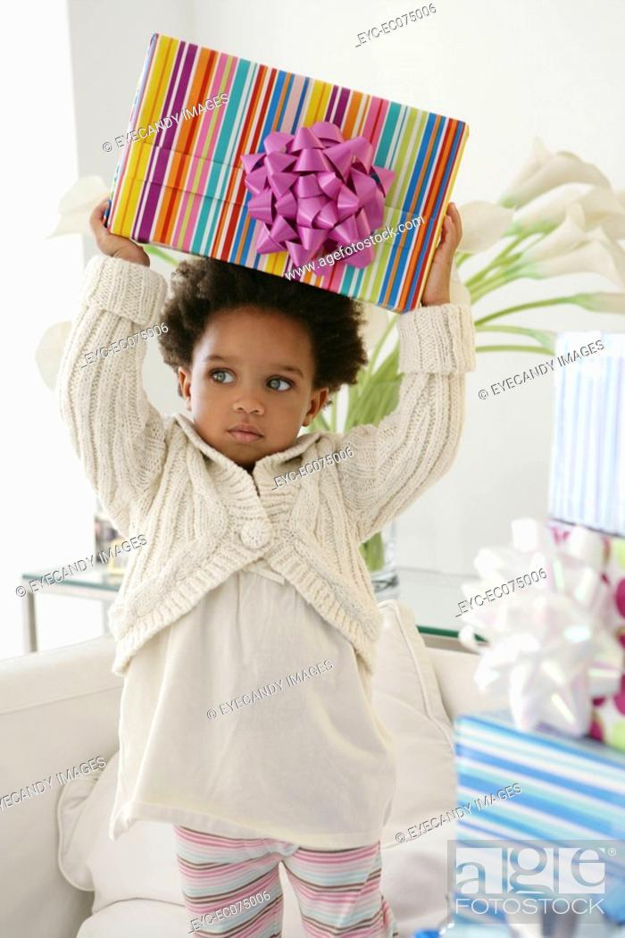 Stock Photo: African American child holding birthday present.