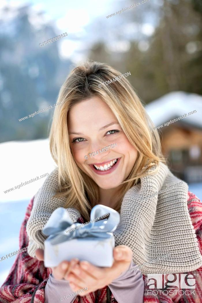 Stock Photo: Portrait of smiling woman holding Christmas gift in snow.