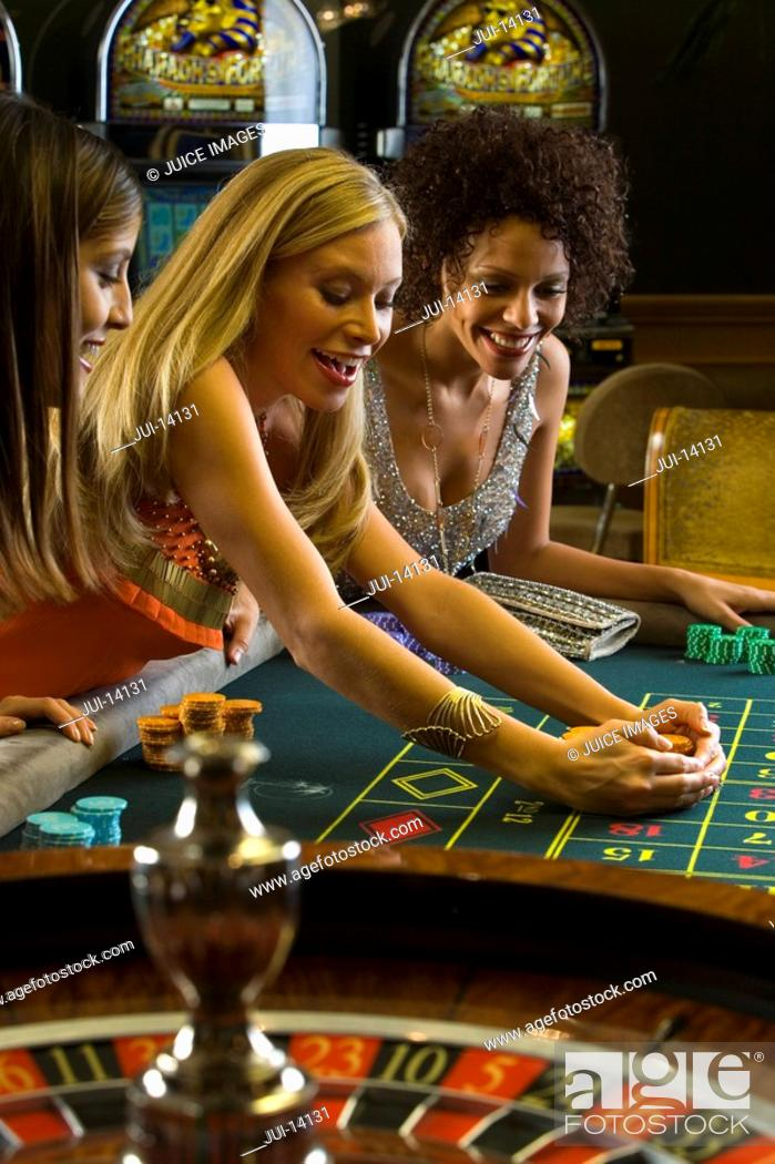 Stock Photo: Young woman collecting pile of gambling chips at roulette table, smiling.