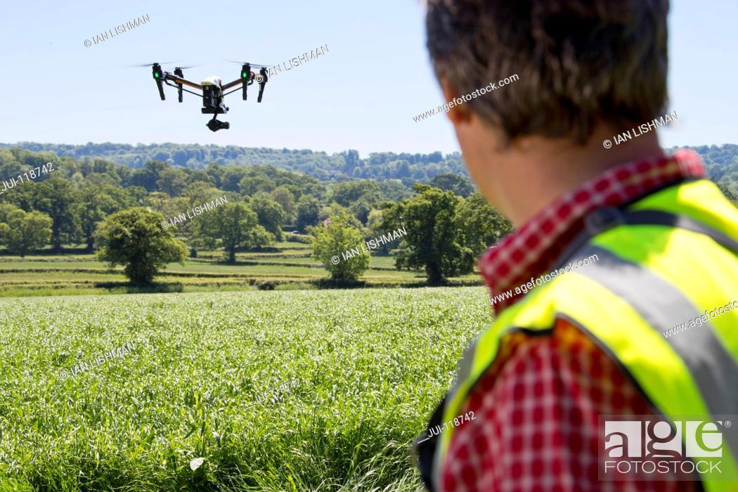 Stock Photo: Farmer flying drone to survey crop in field.