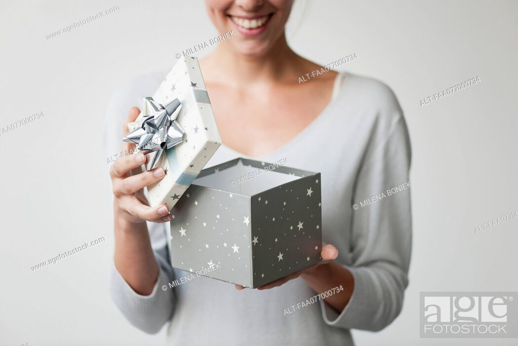 Stock Photo: Woman opening gift box, cropped.