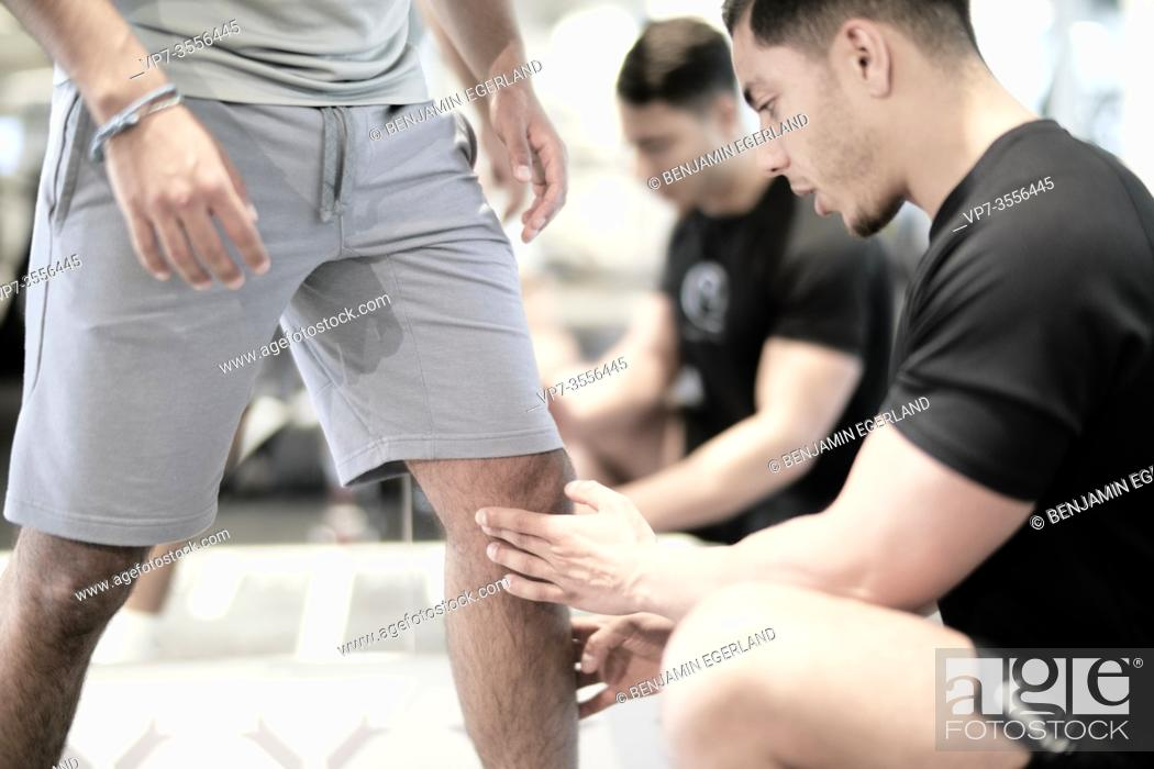Stock Photo: Personal trainer assisting man exercising in gym.