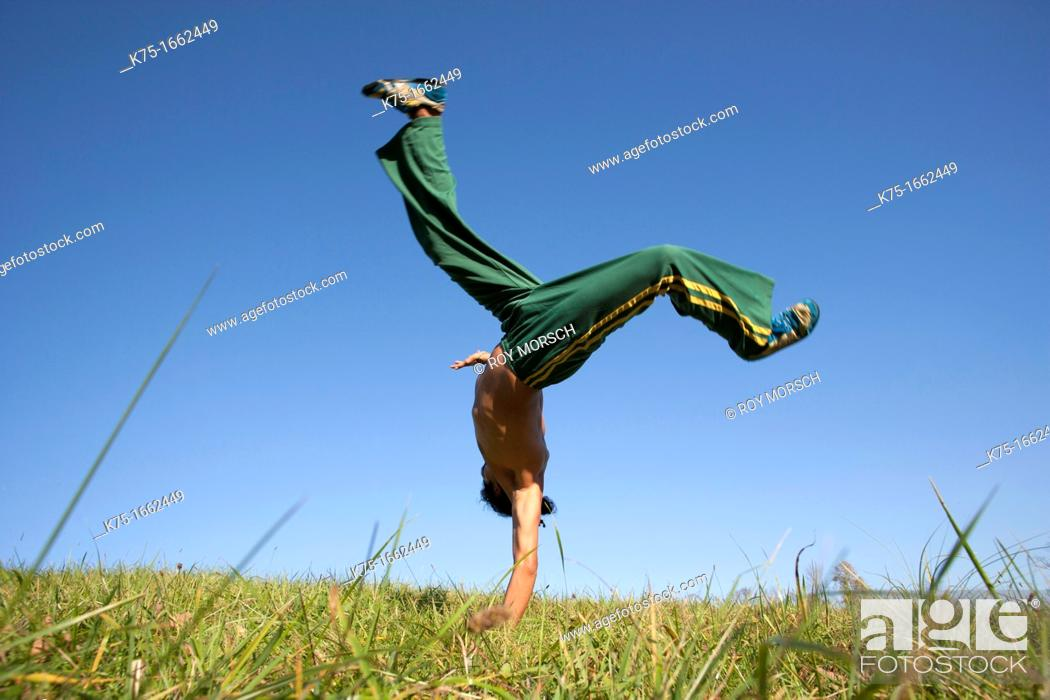 Stock Photo: Man practicing capoeira in field.