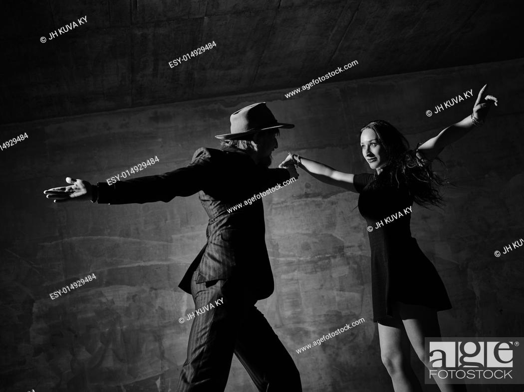 Stock Photo: Man and woman dancing, urban dancing theme, concrete building surroundings, black and white image.