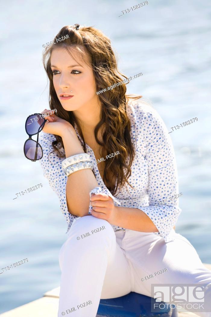 Stock Photo: Attractive young woman with spectacles in hand.