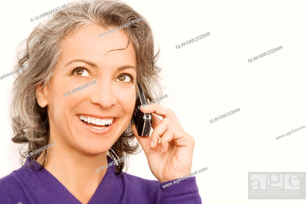 Stock Photo: Close-up of a businesswoman talking on a mobile phone and thinking.