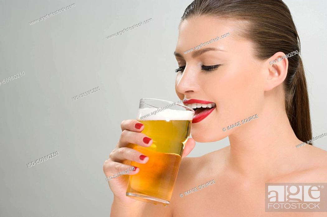 Stock Photo: Woman drinking a pint of lager.