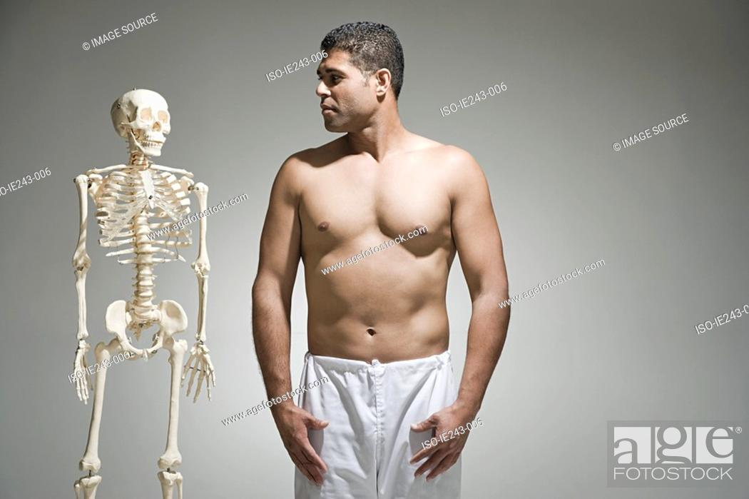 Stock Photo: Man standing by a skeleton.