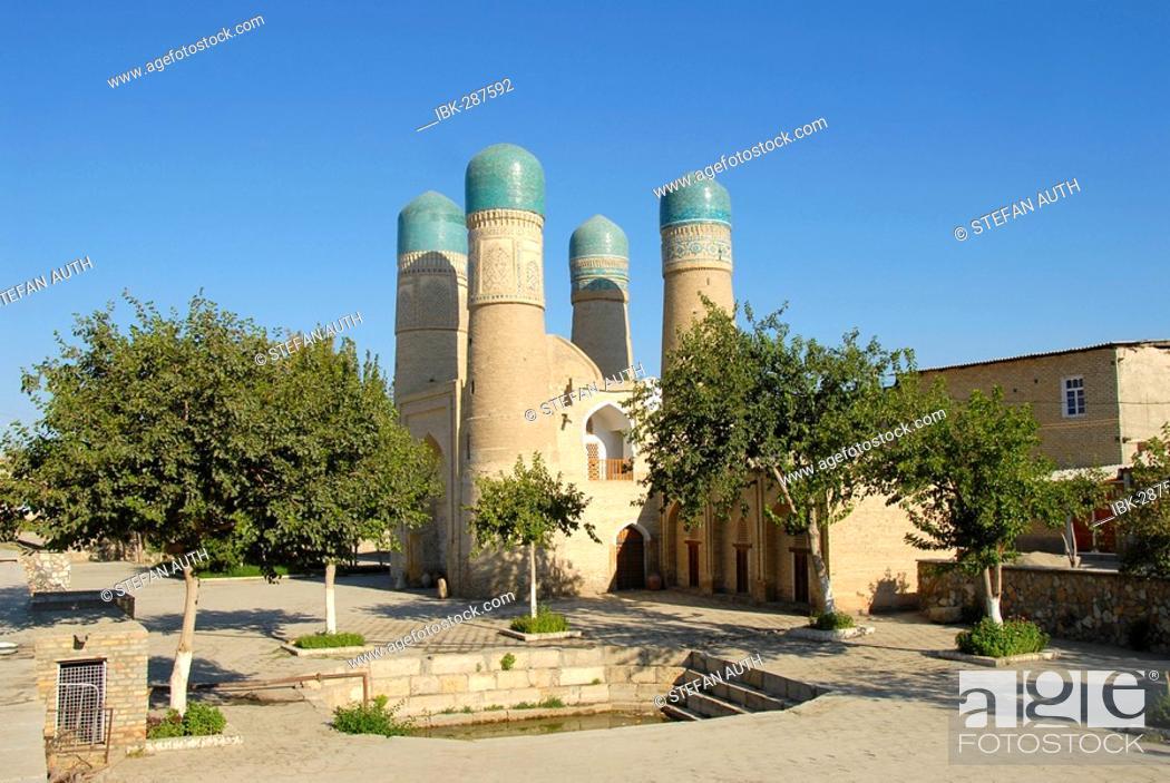 Stock Photo: Four minarets Char Minar gatehouse behind trees Bukhara Uzbekistan.