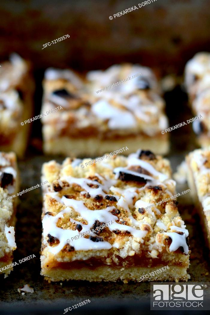 Photo de stock: Apple cake slices with icing on a baking tray.