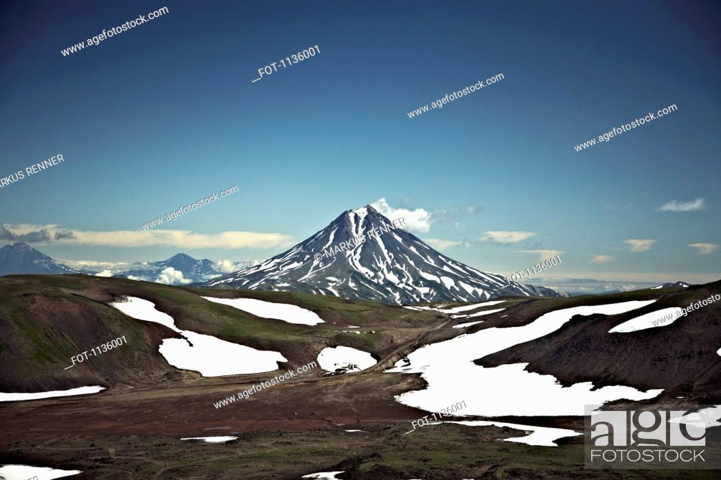 Stock Photo: Patches of snow in a valley in front of Koryaksky Volcano, Russia.