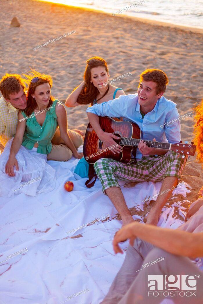 Stock Photo: Young man playing guitar on the beach, Dalmatia, Croatia.