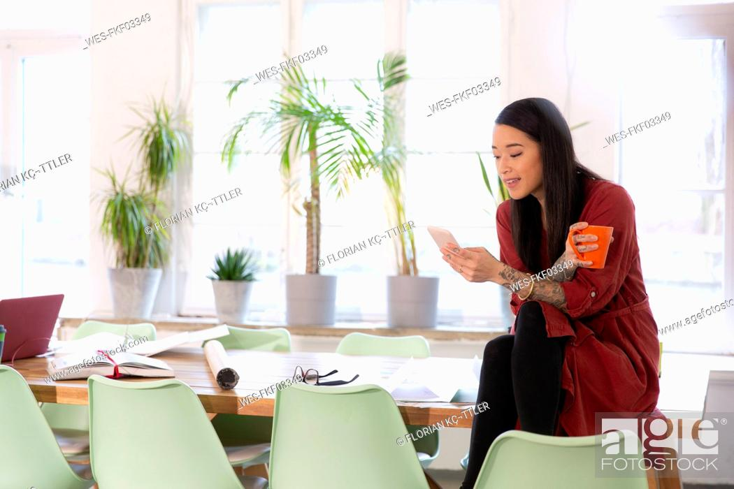 Stock Photo: Woman using cell phone in modern office.
