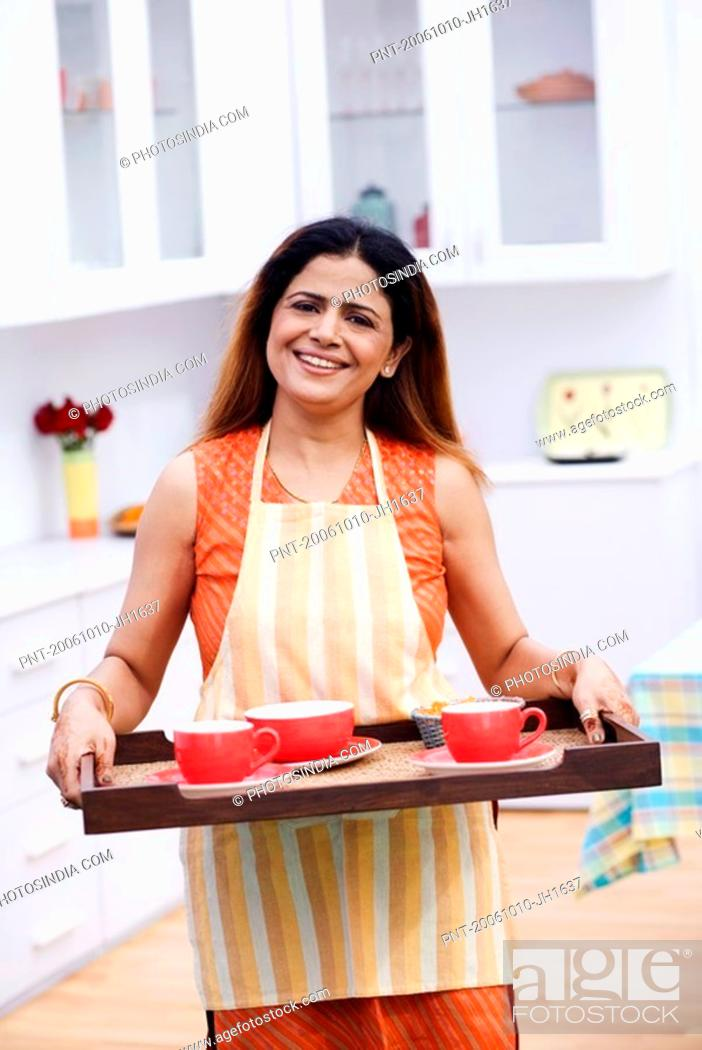Stock Photo: Portrait of a mid adult woman holding a serving tray and smiling in the kitchen.