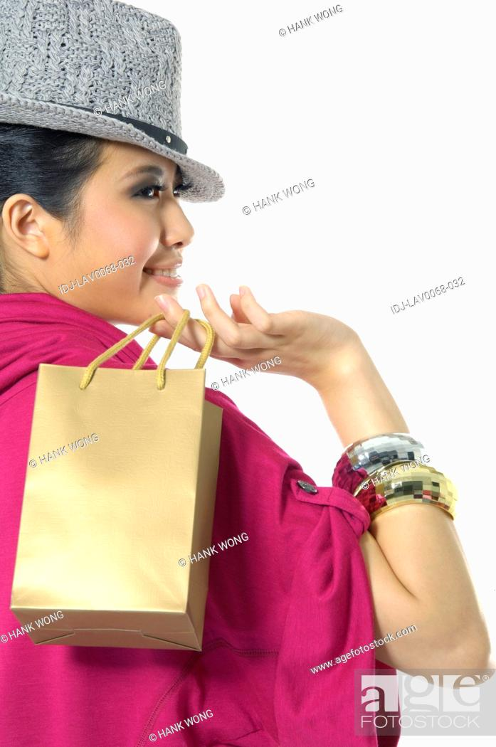 Stock Photo: Woman carrying a shopping bag and smiling.