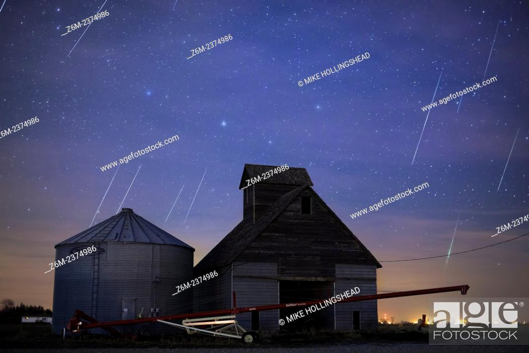 Stock Photo: Geminid meteors streak across the sky behind a barn in western Iowa.