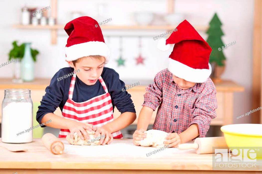 Stock Photo: Two young brothers in colourful festive red Santa hats baking Christmas cookies standing side by side at the kitchen counter each kneading their pastry.