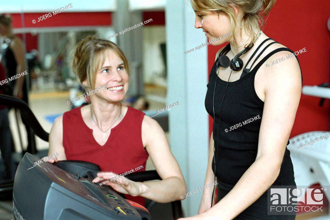 Stock Photo: Young woman at the gym, fitness center, walking on the treadmill, instructed by a coach.